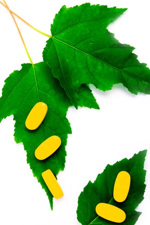 yellow vitamin pills over green leaves on white background photo