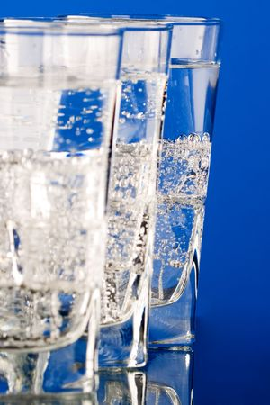 three glasses with cold water closeup on blue background photo