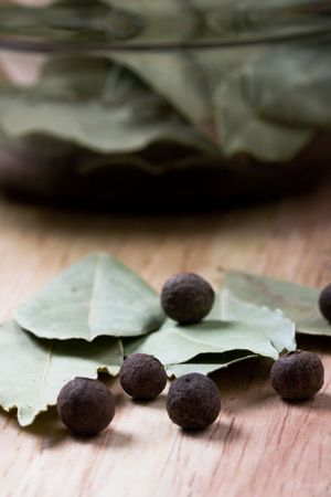 spices: aromatic pepper and bay leaves closeup on wooden background  photo