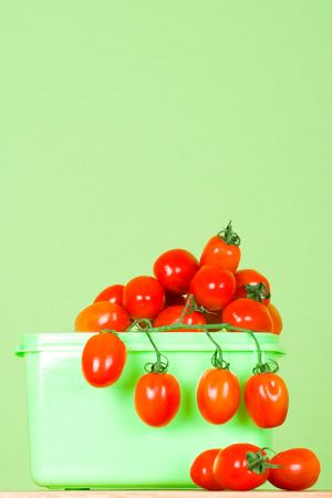 container with fresh tomatoes on green background Stock Photo - 7333629