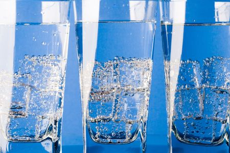 three glasses with cold water on blue background photo