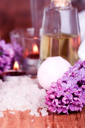 bath and spa items (salt, oil, lilac, candle) on wooden background photo