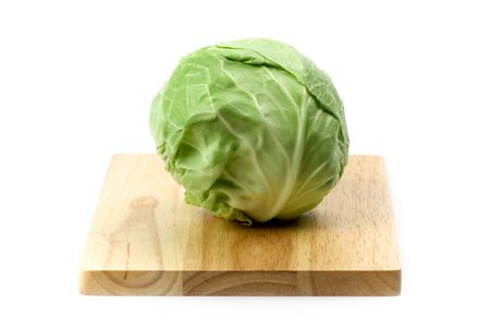 green cabbage on wooden chopping board on white background photo