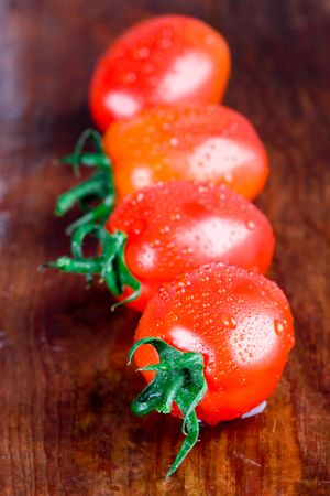 macro images of four wet tomatoes closeup on wooden table photo