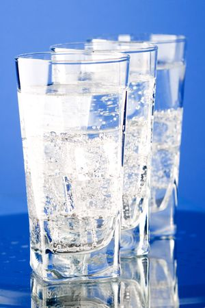 three glasses with cold water on blue background Stock Photo - 7333635