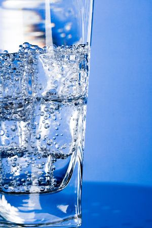 glass with cold water on blue background photo