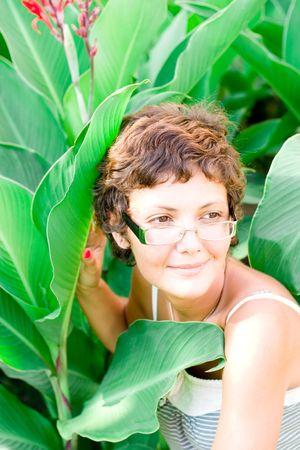 portrait of attractive brunet woman on eyeglasses in a garden photo
