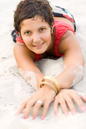 portrait of attractive brunet woman in red lying on a sand photo