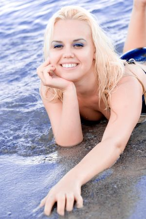 attractive blond woman lying in water and enjoying bathing in the sea photo