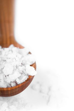 bath and body: bath salt on a wooden spoon closeup on white background
