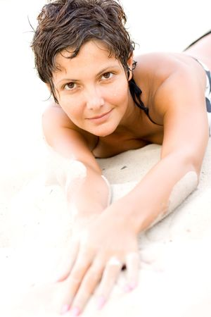 portrait of attractive brunet woman lying on a sand photo