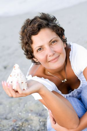 attractive brunet woman on seacoast with a cockleshell in hands  photo