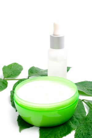 cosmetics with green leaf on white background photo