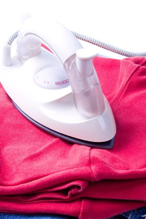 electric iron and pile of clothes on white background photo
