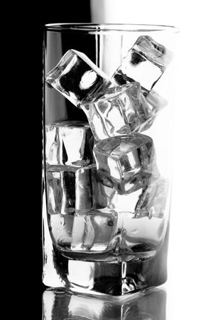 glass with ice cubes isotated on white an black background photo