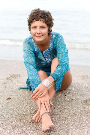 beautiful brunet woman in blue dress on the beach photo