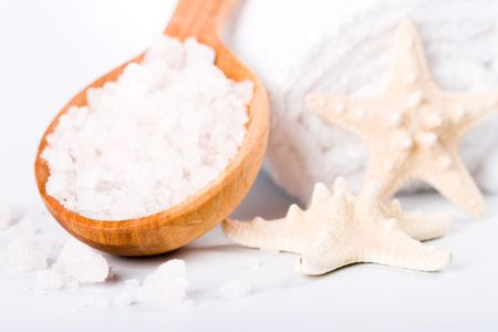 spa products: sea salt on wooden spoon, towel and starfish closeup photo