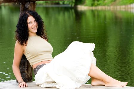 attractive brunet woman sitting near the water photo