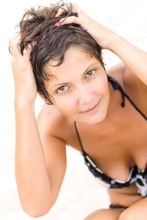 portrait of attractive brunet woman lying on a sand Stock Photo - 7715455