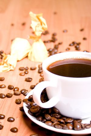 cup of coffee, some sweets and beans on wooden table Stock Photo - 7715411