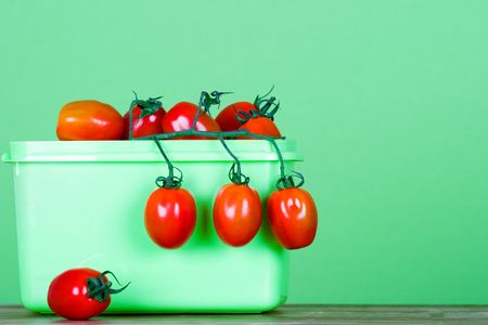 container with fresh tomatoes on green background Stock Photo - 7715412