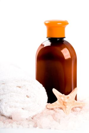 spa products: sea salt, towel, body lotion and seastar closeup on white background photo