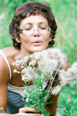 portrait of attractive brunet woman on eyeglasses in a meadow photo