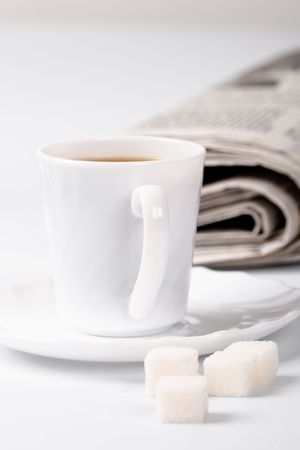 cup of coffee, sugar and stack of newspapers closeup photo