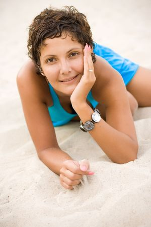portrait of attractive brunet woman in blue dress lying on a sand photo