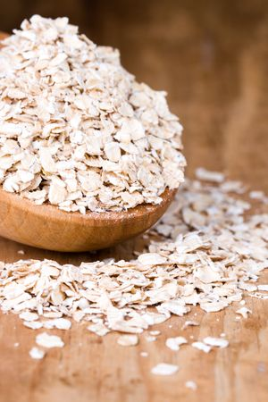 oat flakes in wooden spoon closeup photo