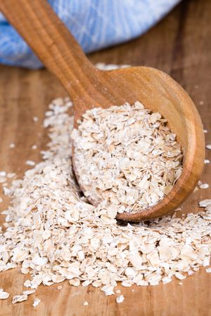 oat flakes in wooden spoon closeup on wooden background photo