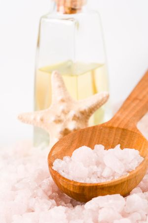 spa products: sea salt on wooden spoon, towel, oil and stars photo