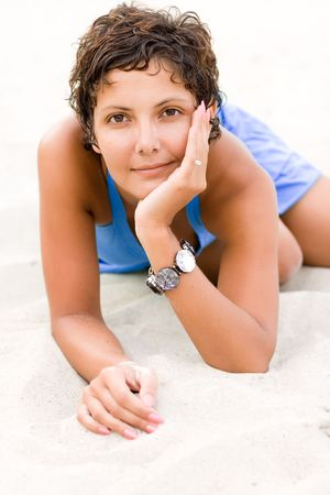 portrait of attractive brunet woman in blue dress lying on a sand Stock Photo - 7716128