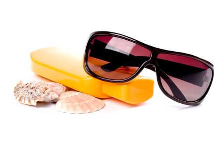 sunglasses, shells and lotion closeup on white background photo