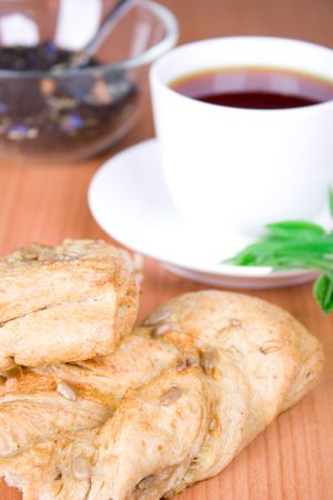cup of black tea with herbs and bread closeup photo