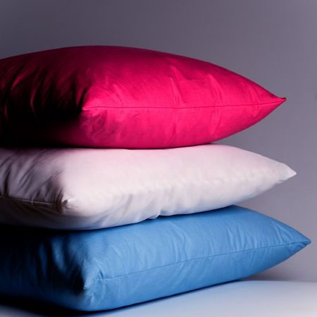 bed spreads: pink, white and blue pillows close up Stock Photo
