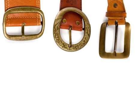 buckles: three brown leather belts with bronze buckles isolated on white background