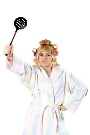 portrait of funny housewife with curlers and skimmer isolated on white background photo