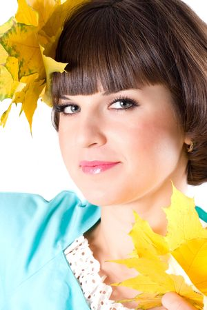 closeup portrait of beautiful young woman with yellow leaves on white background photo