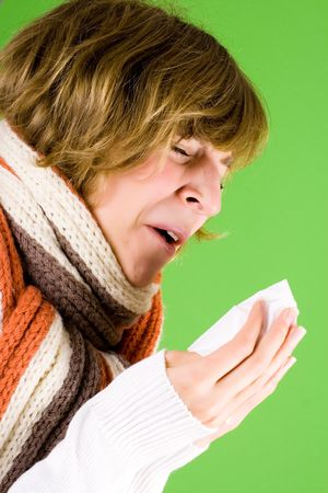 portrait of a cold girl sneezes on green background photo