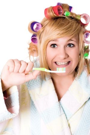 closeup portrait of funny housewife with curlers and toothbrush on white background photo