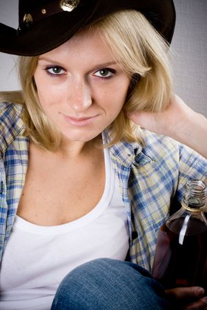 pretty western woman in cowboy shirt and hat with bottle of whiskey Stock Photo - 8157150