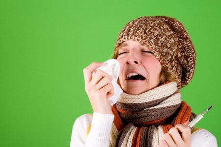 portrait of a cold girl sneezes with handkerchief and thermometer on green background Stock Photo