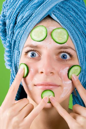 portrait of smiling woman in blue towel and mask from cucumber on green background photo