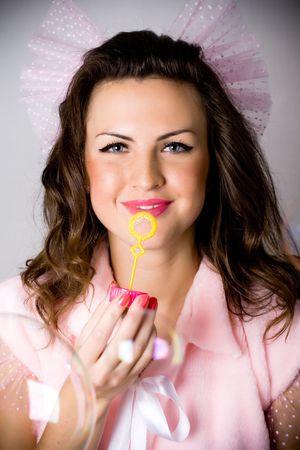 closeup portrait of pretty girll  blowing soap bubbles photo