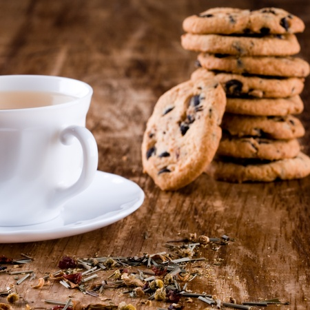 cup of herbal tea and some fresh cookies closeup on wooden table  photo