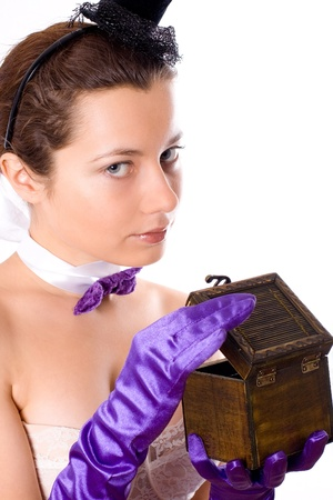 portrait of young attractive woman in corset and little hat with empty wooden box on white background photo