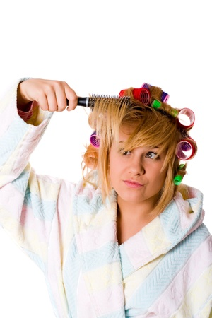closeup portrait of housewife with hairbrush and curlers on white background photo