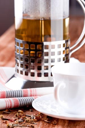 french press with herbal tea and cup closeup on wooden table photo
