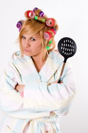 portrait of funny housewife with curlers and skimmer  photo